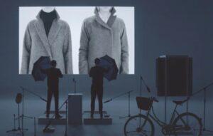 due uomini stanno riporducendo i suoni che emettono i vestiti attraverso oggetti di uso quotidiano, in questa immagine stanno utilizzando due ombrelli