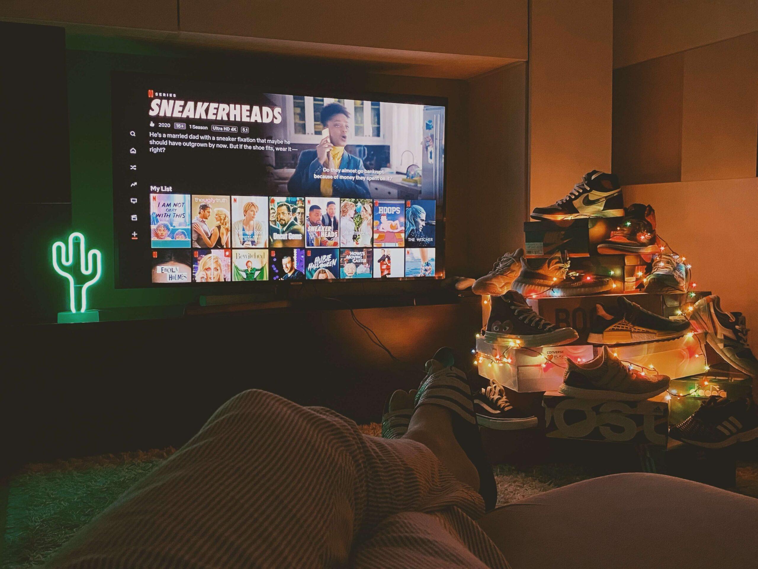 collezione di scarpe di fianco al televisore sintonizzato su Netflix